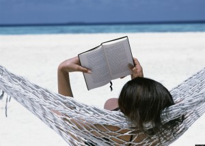 Reading a book on the beach with Yoga Escapes